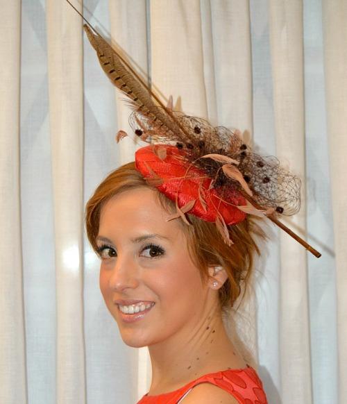 Tocado rojo coral con tul de plumetti marrón pluma de faisan raquis y plumas pequeñas para vestido rojo coral boda de día